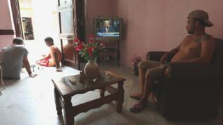 Un cubano ve el discurso de Trump desde el televisor de su casa mientras dos jóvenes juegan ajedrez en el portal.