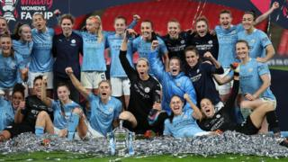 Manchester City players celebrate winning the Women's FA Cup trophy