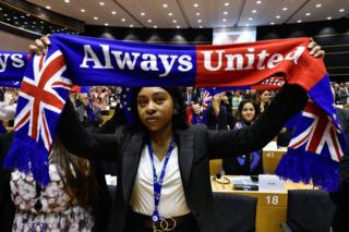 A member of the Group of the Progressive Alliance of Socialists and Democrats in the European Parliament holds a scarf depicting the European Union and the Union Jack flags during a ceremony at the Europa Building in Brussels.