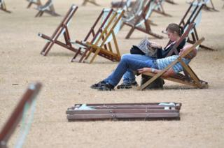 A couple relax on deckchairs on parched grass in Hyde Park in London.