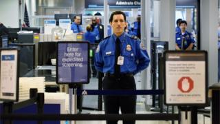 TSA security officer stands at a checkpoint