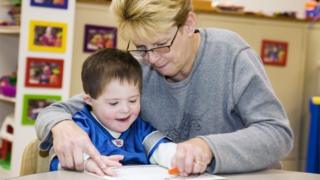 Teacher helps a boy to write at a school for children with special educational needs.
