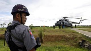 Police stands guard near the military transport helicopter at Maungdaw township in Rakhine State, western Myanmar, 27 September 2017