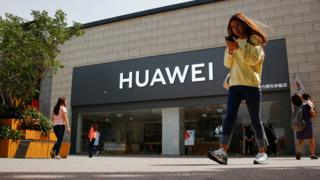 File photo of a person walking past a Huawei shop in Beijing