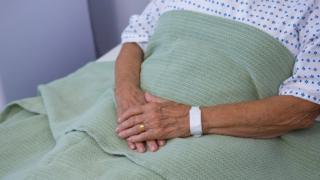 Old person's hands on hospital bed
