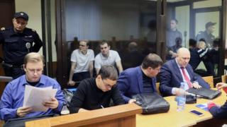 Vyacheslav Kryukov (far left) and Ruslan Kostylenkov (2nd left) in court