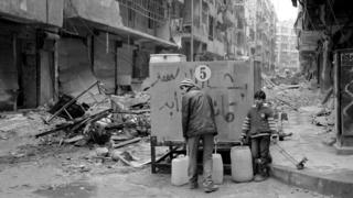 People collect water from a tank in eastern Aleppo