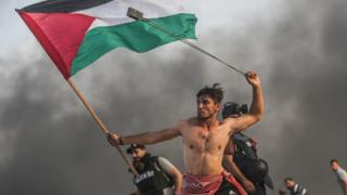 Palestinians throw stones and burn tires in response to Israeli forces during a maritime demonstration in Gaza by October 22, 2018.