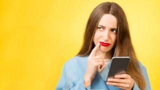 Portrait of confused woman with mobile phone on the yellow background