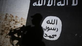 Irak'ta güvenlik görevlileri IŞİD bayrağı önünde