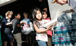 Children receive food at the annual Thanksgiving in the Park gathering where residents of the farm worker community of Immokalee are provided with a free Thanksgiving meal on November 22, 2018 in Immokalee, Florida