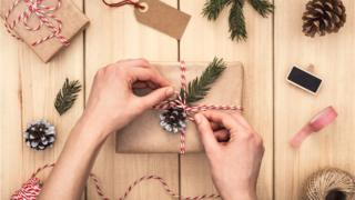 Hands wrapping a gift over wooden table. Top view of Woman preparing present. Directly above. Christmas time.