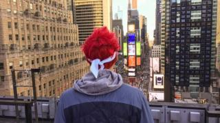 Ninja looks out over a skyscape of New York. His two trademarks are most visible - fluorescent, coloured hair and a bandana.