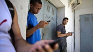 Cubanos con sus teléfonos celulares en La Habana.