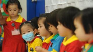 A masked girl sits with classmates at a kindergarten in a residential estate in Hong Kong on June 11, 2009. Hong Kong authorities on June 11 ordered all primary schools in the city to be closed for two weeks after the first cluster of local swine flu cases was found.