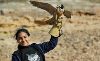 A girl holds a falcon near October city on the outskirt of Cairo, Egypt - Friday 7 February 2020