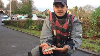 Peter Dennis holds a baby pike