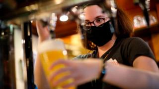 Woman pouring pint in pub