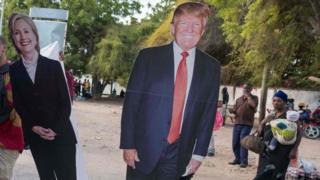 Cut outs of Hillary Clinton and Donald Trump are loaded onto a bus in Dar es Salaam, Tanzania on 7 November 2016
