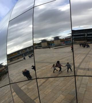 Reflections of people walking by a silver mirrored ball