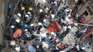 Rescue workers and residents search for survivors at the site of a collapsed building in Mumbai, India, July 16, 2019