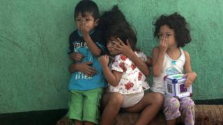 Children cover their faces outside their house while a health ministry worker fumigates to kill mosquitoes