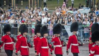 Tourists outside Buckingham Palace watching as guardsmen take part in the Changing of the Guard in central London