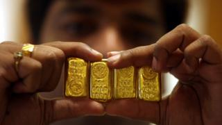 A salesman holds gold bars (file photo)