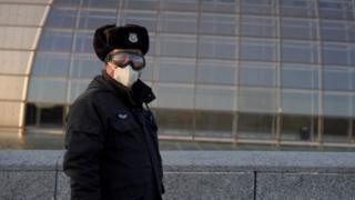 رجل صيني يلبس قناعاً واقياً من عدوى فيروس كورونا