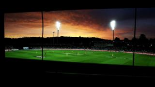 The light towers of Manuka Oval are lit up in front of the sunset.
