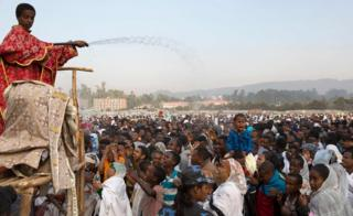 A clergy boy sprays blessed water onto patrons of the Ethiopian Orthodox church during the Timket, an Epiphany festival, in Addis Ababa, on January 19, 2018.