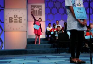 A young girl stretches as she waits for her turn in the spelling bee