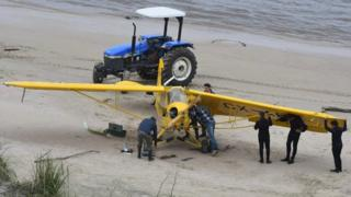 People inspect the yellow plane on the beach