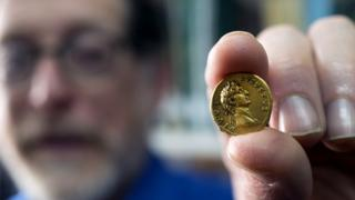 Man holds small gold in his fingers