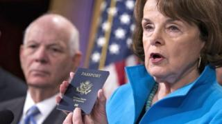 Senate Intelligence Committee Vice Chair Sen Dianne Feinstein, joined by Sen Ben Cardin, points to the embedded chip in her passport that contains digital information at a news conference in Washington on 19 November