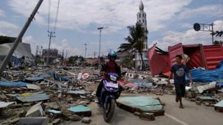 Residents make their way along a street full of debris after an earthquake and tsunami hit Palu, Indonesia. Photo: 29 September 2018