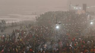 In the smog, a large crowd of Hindu worshippers entering the River Yamuna
