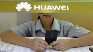 A sales assistant looks at her mobile phone as she waits for customers behind a counter at a Huawei booth in Wuhan, China