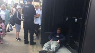 Man slumped in doorway in Manchester with policeman nearby