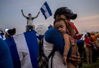 A father holds his son during one of the many demonstrations calling for the resignation of President Ortega in April 2018.