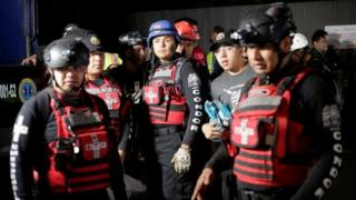 Members of a rescue team wait outside a building after a structural collapse in a car park under construction in Mexico City, Mexico April 10, 2017.