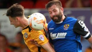 Aaron Collins of Newport County and Dean Wells of Stevenage challenge for the ball