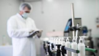 Frascos de creme em close em um laboratório; ao fundo homem com jaleco branco, máscara e protetor de cabelo olha algo em uma tele