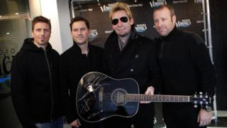 Members of Canadian rock band Nickelback pose with a signed guitar in Naarden
