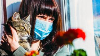 A woman with a cat in a protective mask