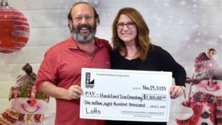 Пара тримає чек на виграш у лотерею