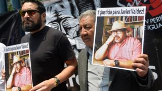 Two men holding up pictures of Javier Valdez