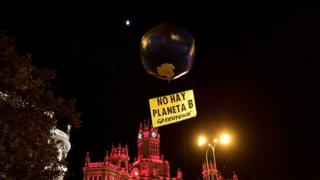 "A balloon in the shape of the Earth is pictured with a placard reading ""there is no Planet B"""