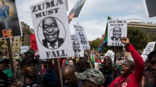 "Protest of people wey dey hold sign wey talk say ""Zuma must Fall"" and ""Despicable Me"""