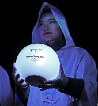 A woman holds a glowing ball with the Pyeongchang Olympics 2018 on